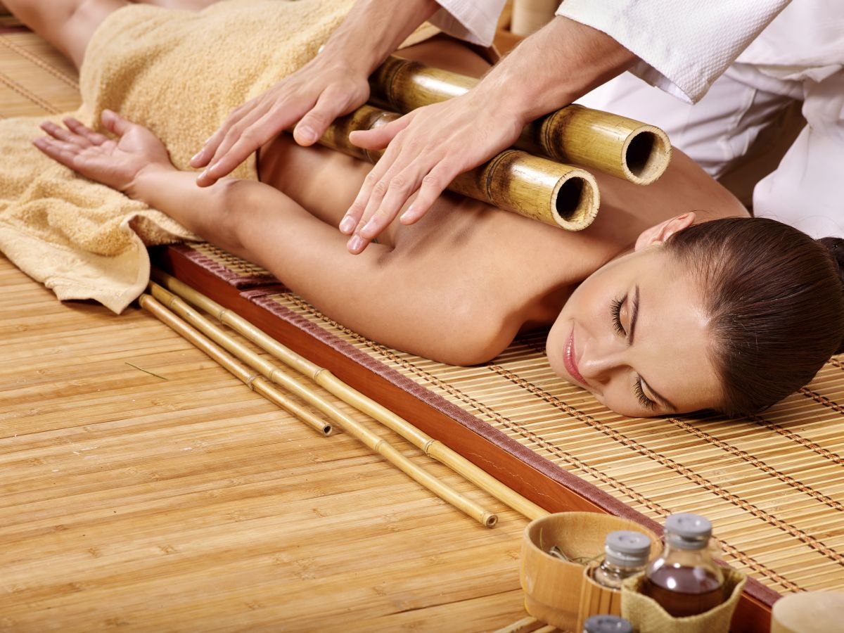 Young woman getting bamboo massage. Male therapist.